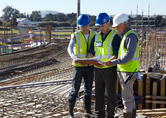 Osoby wkaskach ochronnych oglądają plany naplacu budowy